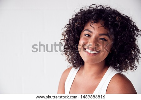 Portrait Of Smiling Casually Dressed Woman In Vest Top Standing Against White Brick Studio Wall #1489886816