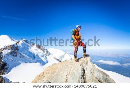 Alpinist guy mountaineer man standing posing Mont Blanc du Tacul snow mountain summit. Chamonix valley view beautiful landscape, Europe France Alps range tourism. Royalty-Free Stock Photo #1489895021