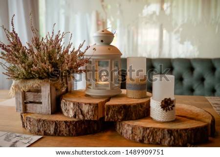 Pink heather in in wooden box. Interior decor with candles, lantern, heather, cozy decoration. Weeding decor for table. Autumn mood.blooming forest heather in basket. #1489909751