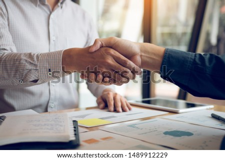Entrepreneurs collaboration deal shaking hands in a modern office and financial paper graph on desk. #1489912229