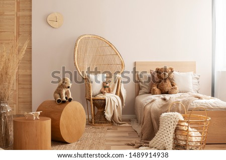 Wicker peacock chair with pillow, armchair and toy in beige and wooden baby bedroom interior #1489914938