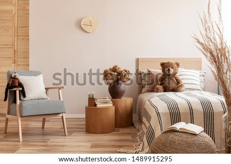 Flowers in brown vase on wooden nightstand table next to single bed with stripped bedding with teddy bear #1489915295