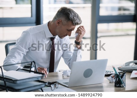 selective focus of upset man holding crumpled paper ball near laptop  #1489924790