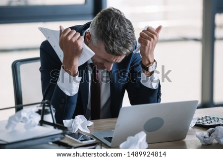 selective focus of frustrated man in suit holding crumpled paper near laptop  #1489924814