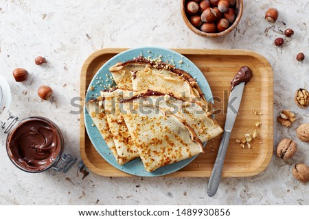 Homemade crepes, tasty thin pancakes with chocolate and nuts.  Royalty-Free Stock Photo #1489930856