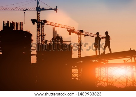 Silhouette Two engineers consult and inspect high-rise construction work over blurred industry background with Light fair. #1489933823