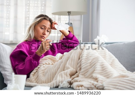 Sickness, seasonal virus problem concept. Woman being sick having flu lying on sofa looking at temperature on thermometer. Sick woman lying in bed with high fever. Cold flu and migraine. Royalty-Free Stock Photo #1489936220