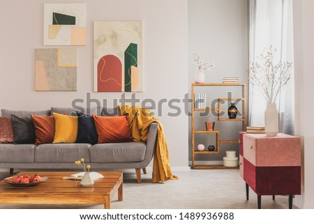 Yellow, orange, black and brown pillows on comfortable grey scandinavian sofa in bright living room interior with abstract paintings on the wall #1489936988