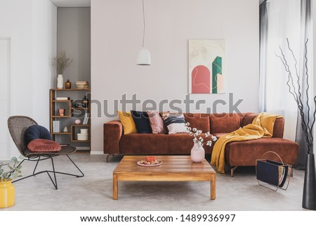 Flowers in vase on wooden coffee table in fashionable living room interior with brown corner sofa with pillows and abstract painting on the wall #1489936997