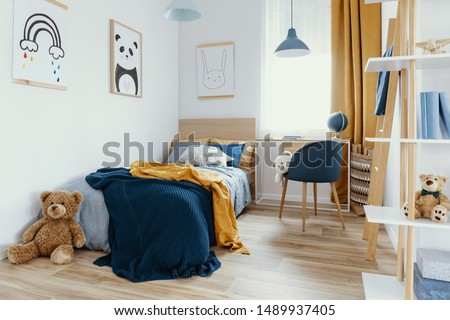 Workspace with desk and chair in elegant teenager's room with blue and orange design #1489937405