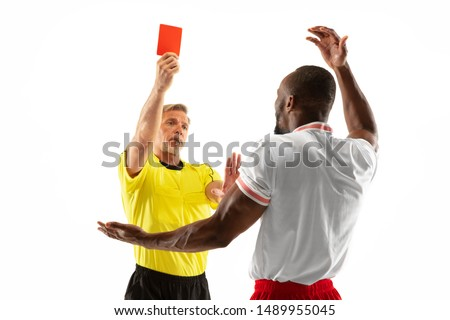 Referee showing a red card to a displeased african-american football or soccer player while gaming isolated on white background. Concept of sport, rules violation, controversial issues, emotions. #1489955045