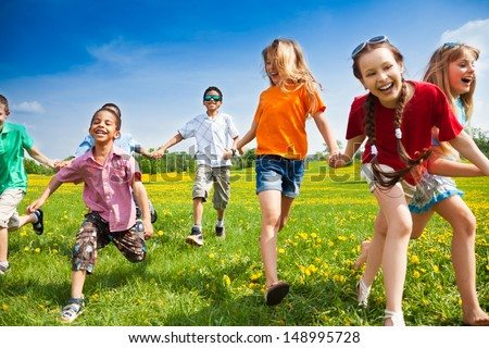 Large group of children running in the dandelion spring field Royalty-Free Stock Photo #148995728