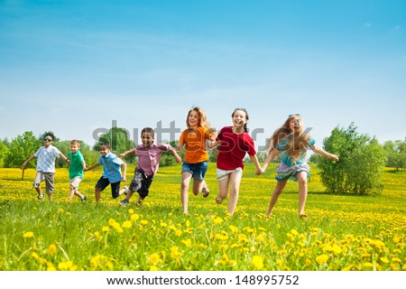 Group of seven running in the park kids, boys and girls, black and Caucasian Royalty-Free Stock Photo #148995752