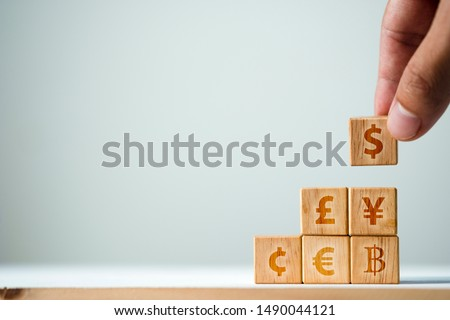 Hand putting wooden cube of US dollar sign to Yuan  Yen Euro and Pound sterling sign.US dollar is main and popular currency of exchange in the world.Investment and saving concept. #1490044121