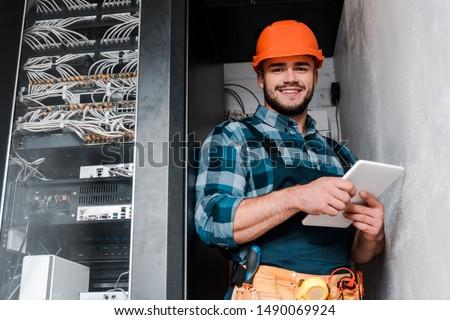 happy bearded technician in safety helmet holding digital tablet  #1490069924