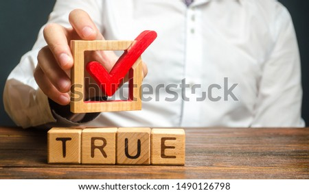 A man holds a red check mark over word True. Confirm the veracity and truth. Fight against fake news hostile propaganda. Confirmation facts, refutation of rumors. Debunking Myths and Misconceptions #1490126798