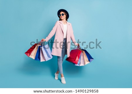 Full length photo of lovely content girl on holiday buy presents for friends wear retro topcoat eyewear eyeglasses denim jeans isolated over pink background #1490129858