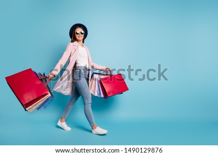 Full size photo of cute pretty cheerful lady in eyeglasses eyewear go shopping for bargains wear season cote denim jeans isolated over blue background #1490129876