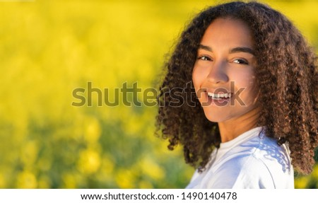Beautiful mixed race biracial African American girl teenager female young woman smiling and happy in a field of yellow flowers  #1490140478