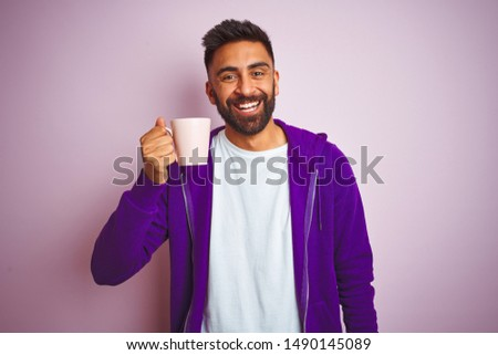 Indian man wearing purple sweatshirt drinking cup of coffee over isolated pink background with a happy face standing and smiling with a confident smile showing teeth #1490145089