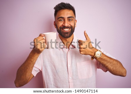 Young indian man wearing shirt drinking cup of coffee standing over isolated pink background happy with big smile doing ok sign, thumb up with fingers, excellent sign #1490147114