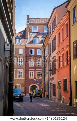 Warsaw, Poland - July 2, 2019: Streets of the old city. Polish ancient architecture. European city - tourist route attractions. Attraction - colorful houses, paving stones in the streets. #1490185124