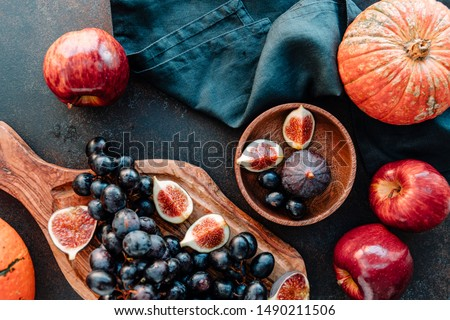 Top view of Autumn food still life with season fruits and vegetables like Bangalore blue grape, red apples, pumpkins and figs on a table.  Royalty-Free Stock Photo #1490211506