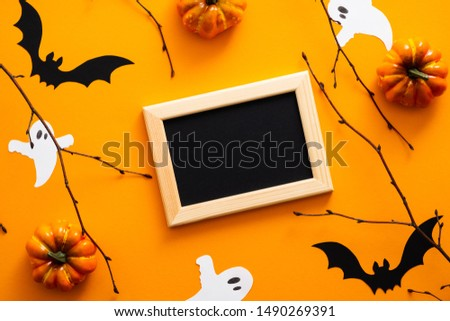 Happy halloween concept. Halloween decorations, picture frame, pumpkins, bats, ghosts on orange background. Halloween party greeting card mockup with copy space. Flat lay, top view, overhead.