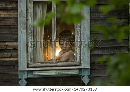 A boy looking at the window with plat band in russian old house. Image with selective focus and toning #1490273159