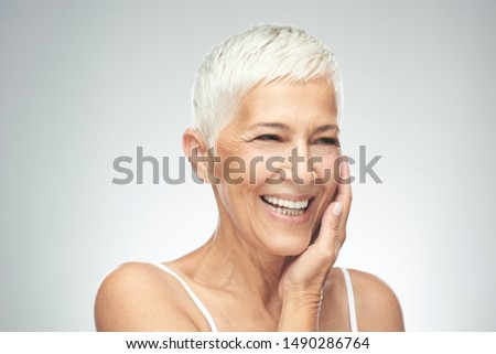 Beautiful smiling senior woman with short gray hair posing in front of gray background. Beauty photography. #1490286764