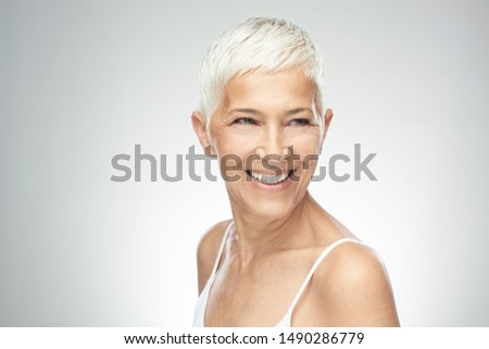 Beautiful smiling senior woman with short gray hair posing in front of gray background. Beauty photography. #1490286779