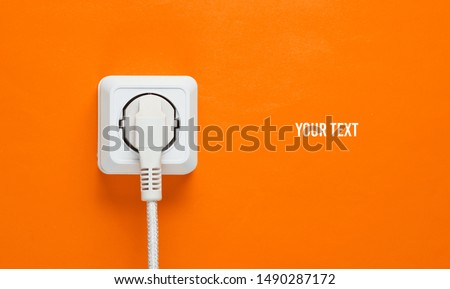 White cable plugged into power outlet on orange wall background with copy space Royalty-Free Stock Photo #1490287172