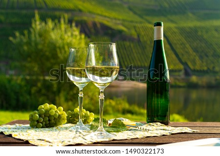 Famous German quality white wine riesling, produced in Mosel wine regio from white grapes growing on slopes of hills in Mosel river valley in Germany, bottle and glasses served outside in Mosel valley #1490322173