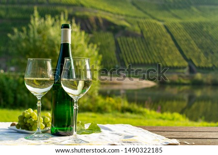 Famous German quality white wine riesling, produced in Mosel wine regio from white grapes growing on slopes of hills in Mosel river valley in Germany, bottle and glasses served outside in Mosel valley #1490322185
