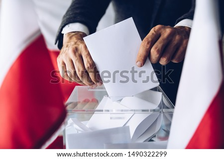 Man putting his vote do ballot box. Political elections #1490322299