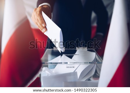 Man putting his vote do ballot box. Political elections #1490322305