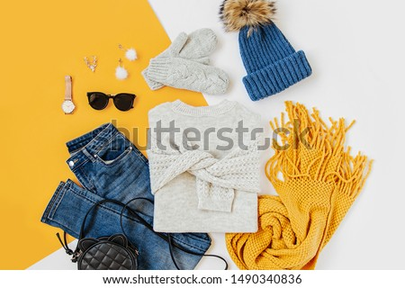Blue winter hat with jeans, sweater, handbag and yellow scarf on white background. Women's stylish autumn or winter outfit. Trendy clothes collage. Flat lay, top view.