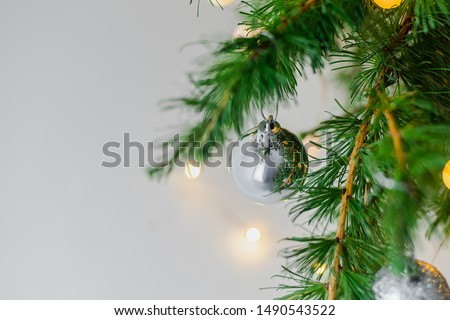 New Year's silver shiny ball hanging on a fir branch. Lights and garlands on a gray snow background. Christmas and happy new year concept, space for text for your design. Wallpaper. #1490543522
