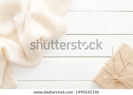 Autumn composition. Feminine desk table with knitted scarf and gift box on wooden white background. Flat lay, top view. Nordic, hygge, cozy home concept #1490565146