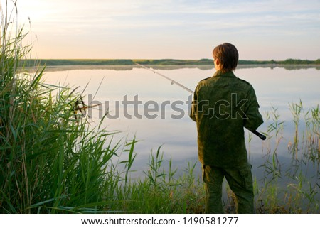 Silhouette of a man fishing. Beautiful picture of a guy at dawn on vacation, holding a fishing rod, fishing.