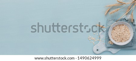 bowl of dry oat flakes with ears of wheat on light blue background. Cooking oats porridge concept. Top view with free space for text on banner #1490624999