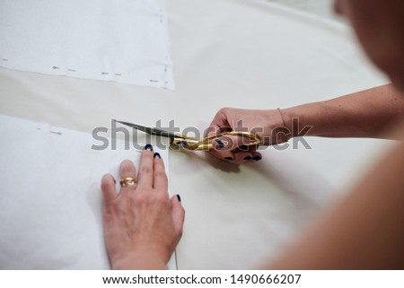 Hands with scissors with golden handles, cutting paper pattern with light beige fabric. Close-up picture of cutting process. Sewing tutorial. Pattern making workshop by fashion designer.