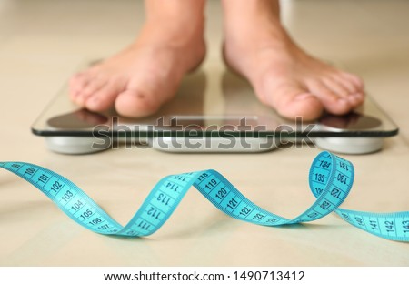 Tape in front of woman standing on floor scales indoors. Overweight problem #1490713412