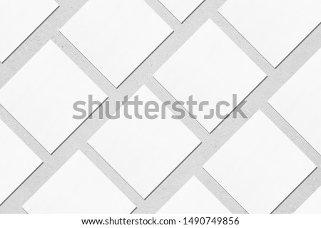 White empty square business card mockups with soft shadows lying diagonally on neutral light grey concrete background. Flat lay, top view. Open composition.