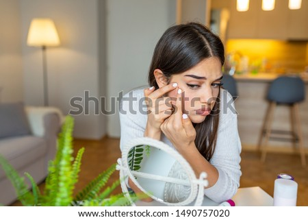 Portrait of beautiful young woman squeezing pimples while looking at the mirror. Pimple on cheek. Young woman squeeze her acne in front of the mirror. I'm sure this will go away if I pop it. #1490757020