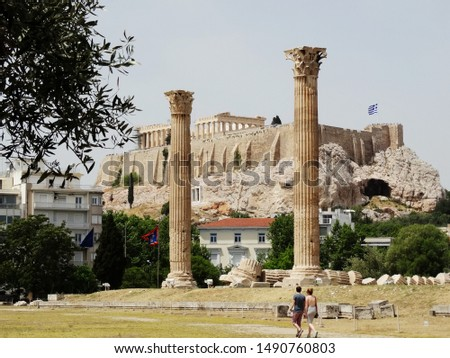 Tourists visit Temple of Olympian Zeus in Athens in Greece with The Parthenon Temple on hill in sight.  Temple of Olympian is also known as the Columns of the Olympian Zeus. #1490760803