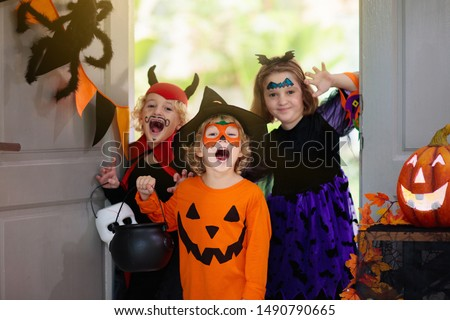 Kids trick or treat on Halloween night. Child at decorated house door. Boy and girl in witch and vampire costume and hat with candy bucket and pumpkin lantern. Autumn decoration. Friends play. #1490790665