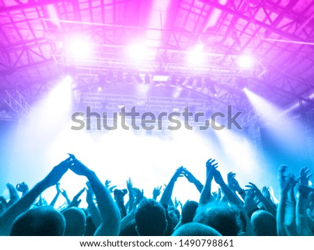Shot taken inside a concert hall, people are visible in front of the stage, clapping and raising their hands #1490798861