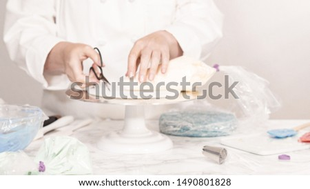 Stacking cake layers to create the round three-layer vanilla cake. #1490801828