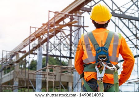 Construction worker wearing safety harness and safety line working at high place,Practices of occupational safety and health can use hazard controls and interventions to mitigate workplace hazards. #1490814092